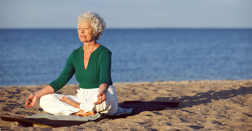 Older woman on beach meditating